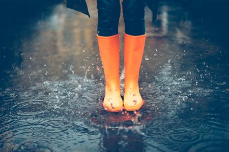 Al sentirse protegida en sus botas. Primer plano de mujer en botas de goma naranja saltando en el charco Foto de archivo - 64573881