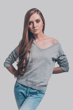 Pure elegance. Studio shot of attractive young woman in casual wear holding hands behind back and looking at camera Stock Photo