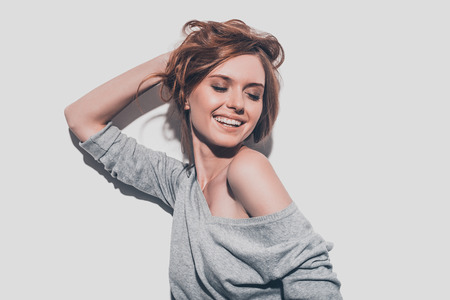 Feeling so happy. Attractive young smiling woman holding hand in hair and keeping eyes closed while standing against grey background