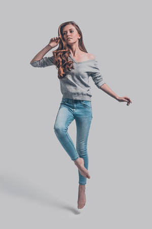 only adult: Jumping beauty. Attractive young woman in casual wear jumping against grey background