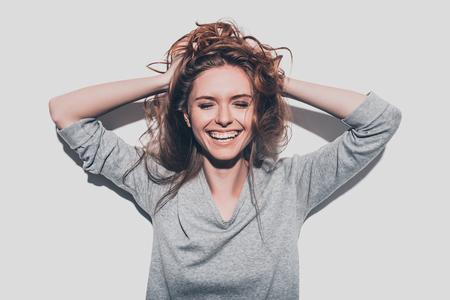 True happiness. Attractive young smiling woman holding hands in hair and keeping eyes closed while standing against grey background Foto de archivo