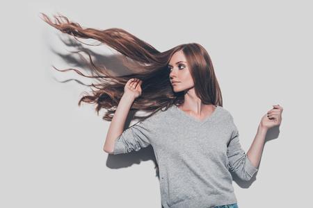 Como un fuego. Mujer joven atractiva con el pelo alborotado mirando a otro lado mientras está de pie contra el fondo gris