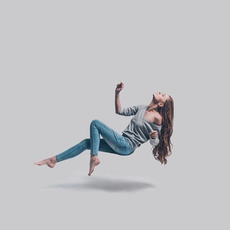 Belleza en el aire Tiro de estudio de longitud completa de mujer joven atractiva flotando en el aire y manteniendo los ojos cerrados