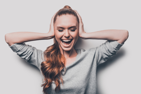 hands covering ears: This is too much! Frustrated young woman covering ears by hands and keeping eyes closed while standing against grey background Stock Photo