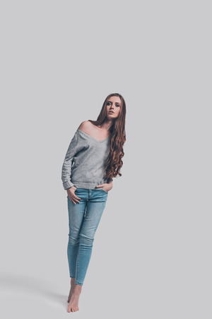 Feeling casual. Full length studio shot of attractive young woman in casual wear looking at camera while posing against grey background
