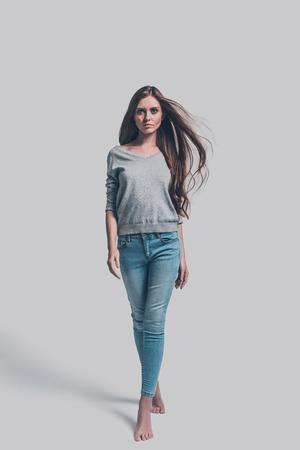 自信を持って、美しい。カジュアル ウォーキング、あなたを見て魅力的な若い女性の完全な長さのスタジオ撮影 写真素材