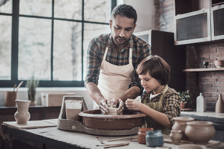 Pottering with son. Confident young man and little boy making ceramic pot on the pottery class