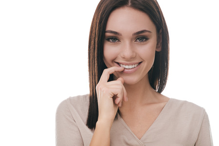 flirty: Feeling flirty. Attractive young woman holding finger in mouth and smiling while standing against white background