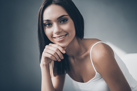 seductress: Beautiful seductress. Attractive young woman holding hand on chin and looking at camera with smile while sitting against grey wall Stock Photo