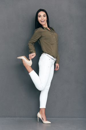 full lenght: Look at my new heels! Full lenght of attractive young woman in smart casual wear posing against grey background and looking happy