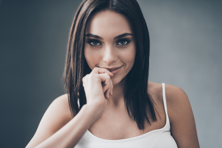 seductress: Flirty seductress. Attractive young woman holding hand on chin and looking flirty while sitting against grey wall