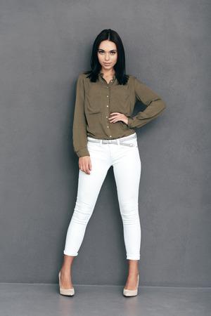 Segura de su estilo. Longitud total de la mujer joven y atractiva en ropa de sport elegante posando sobre fondo gris