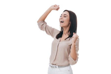puños cerrados: Happy winner. Beautiful young woman in smart casual wear gesturing and looking happy while standing against white background