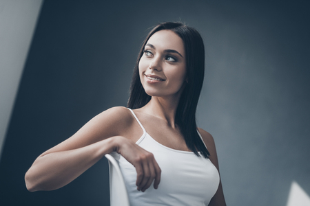seductress: Cheerful seductress. Attractive young woman sitting on chair and looking over shouder with smile while sitting against grey wall Stock Photo