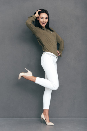 full lenght: Cheerful beauty. Full lenght of attractive young woman in smart casual wear posing against grey background and looking happy