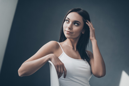 Thoughtful beauty. Attractive young woman sitting on chair and adjusting her hair while sitting against grey wall Stock Photo