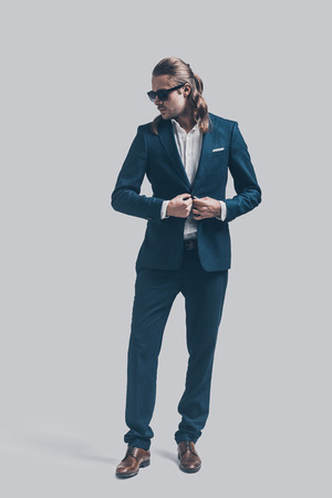 heartbreaker: Handsome heartbreaker. Full length of handsome young man in full suit adjusting his sunglasses while standing against grey background