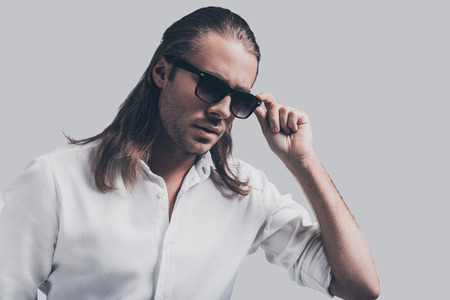 male fashion model: Charming heartbreaker. Handsome young man in white shirt adjusting his sunglasses while standing against grey background Stock Photo