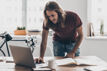 hair man: Man at work. Handsome young man with long hair looking at his laptop while leaning at the desk in creative office Stock Photo