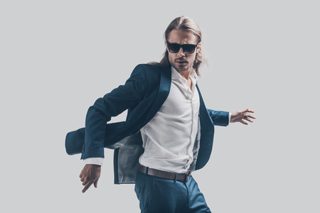 handsome young man: His perfect style in motion. Handsome young man in full suit and sunglasses moving in front of grey background