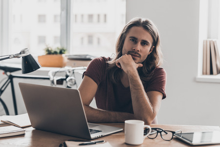 man working computer: How may I help you? Confident young man with long hair holding hand on chin and looking at camera while sitting at his working place in office Stock Photo