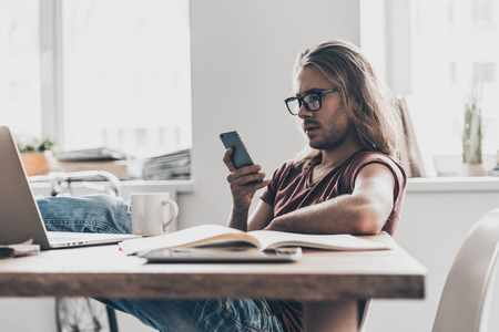 Staying connected. Confident young man with long hair holding smart phone and looking at it while sitting at his working place in office