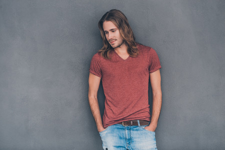 man with long hair: Feeling casual. Handsome young man in casual wear holding hands in pockets and looking thoughtful while standing against grey background