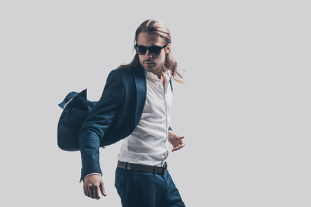 Fühlen frei und bequem in seinem Stil. Gut aussehender junger Mann in voller Anzug und Sonnenbrille vor grauem Hintergrund bewegen