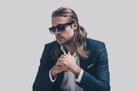 male fashion model: Thoughtful handsome. Handsome young man in full suit and sunglasses holding hands clasped looking thoughtful while sitting against grey background