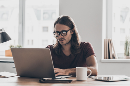 place of work: Concentrated at work. Confident young man with long hair working on laptop while sitting at his working place in office