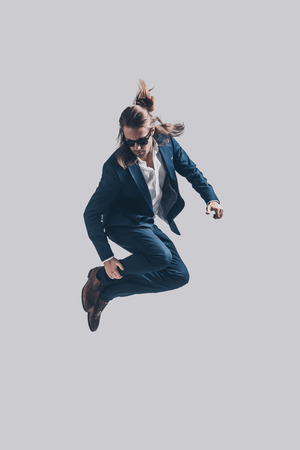 midair: Mid-air style. Handsome young man in full suit and sunglasses jumping against grey background Stock Photo
