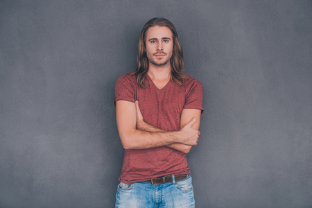 only man: Confident and handsome. Handsome young man in casual wear looking at camera and keeping arms crossed while standing against grey background Stock Photo