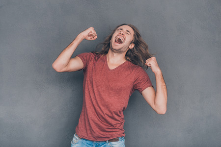 winner man: Everyday winner. Happy young man in casual wear standing against grey background and gesturing Stock Photo