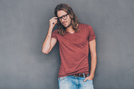 man with long hair: Enjoying his casual style. Handsome young man in casual wear adjusting his eyeglasses and looking thoughtful while standing against grey background Stock Photo