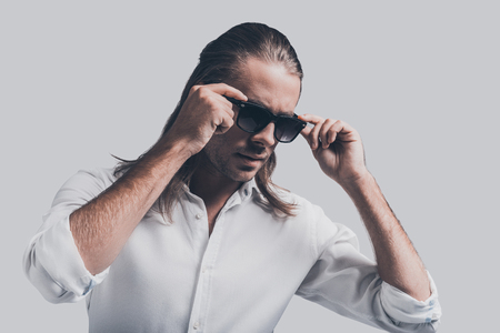 metrosexual: Stylish and handsome. Handsome young man in white shirt adjusting his sunglasses while standing against grey background
