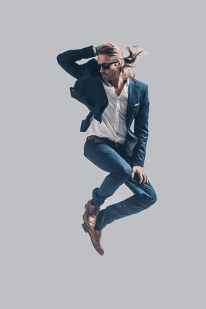 midair: Man in mid-air. Handsome young man in full suit and sunglasses jumping against grey background