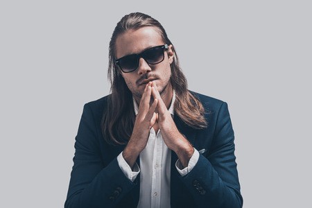 male fashion model: Young and full of confidence. Handsome young man in full suit and sunglasses keeping hands clasped and looking at camera while sitting against grey background