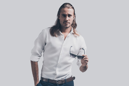male hair: Confident in his perfect style. Handsome young man in white shirt holding his sunglasses and looking at camera while standing against grey background Stock Photo