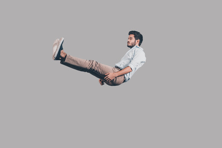 fashion model: Falling down. Mid-air shot of handsome young man falling against grey background