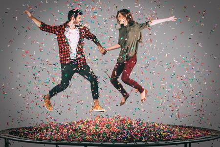 jovenes felices: Les encanta divertirse. disparo en pleno vuelo de hermosa pareja alegre joven de la mano mientras salta en el trampolín junto con confeti a su alrededor