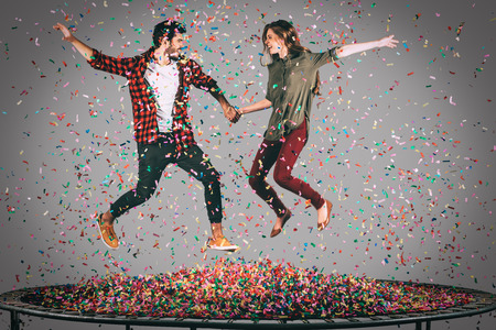 young happy couple: They love having fun. Mid-air shot of beautiful young cheerful couple holding hands while jumping on trampoline together with confetti all around them