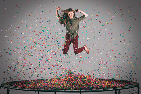 midair: Colorful fun. Mid-air shot of beautiful young woman jumping on trampoline with confetti all around her