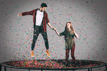 midair: Fun time. Mid-air shot of beautiful young cheerful couple jumping on trampoline together with confetti all around them