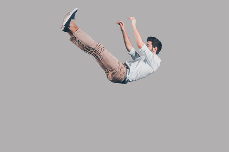 Free falling. Mid-air shot of handsome young man falling against grey background