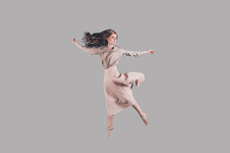 Feeling freedom of every move. Studio shot of attractive young woman hovering in air
