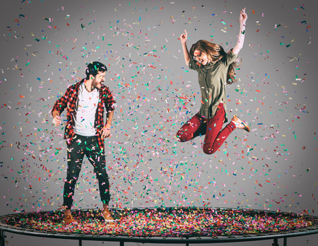 midair: Fun time together. Mid-air shot of beautiful young cheerful couple jumping on trampoline together with confetti all around them