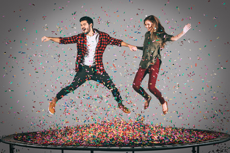 midair: Enjoying fun time together. Mid-air shot of beautiful young cheerful couple holding hands while jumping on trampoline together with confetti all around them