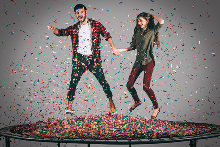 midair: Just for fun. Mid-air shot of beautiful young cheerful couple holding hands while jumping on trampoline together with confetti all around them Stock Photo