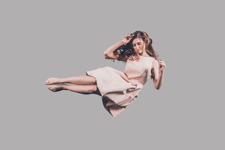 Belleza en el aire Tiro del estudio de la mujer joven atractiva que asoma en el aire