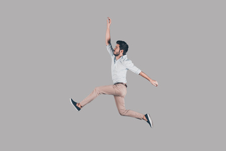 Free jumping. Mid-air shot of handsome young man jumping and gesturing against background